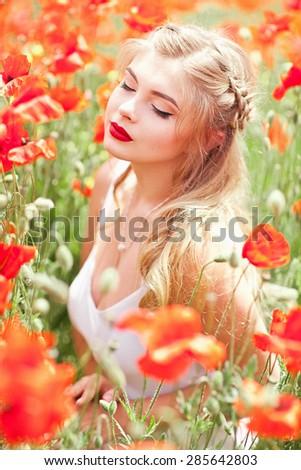 Free Happy Blond Woman Enjoying Nature In Poppy Field. Beauty Girl Outdoor. Freedom concept. Sunbeams. Enjoyment. - stock photo