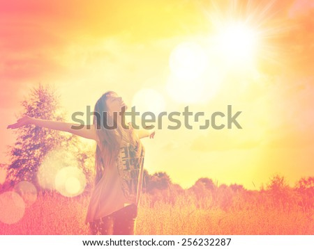 Free Happy Woman Enjoying Nature. Beauty Girl Outdoor. Freedom concept. Beauty Girl over Sky and Sun. Sunbeams. Enjoyment. Summer Meadow. - stock photo