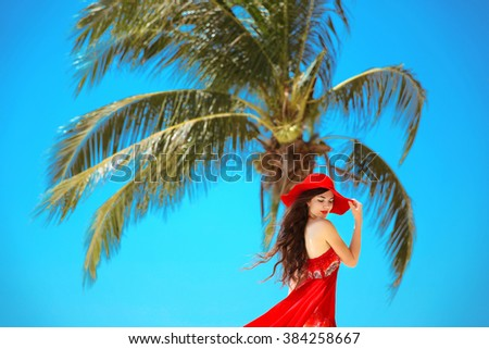 Free Happy Woman Enjoying Nature. Beauty Girl with red hat, summer Outdoor. Freedom concept. Beauty Girl over Sky and Sun. Enjoyment. - stock photo