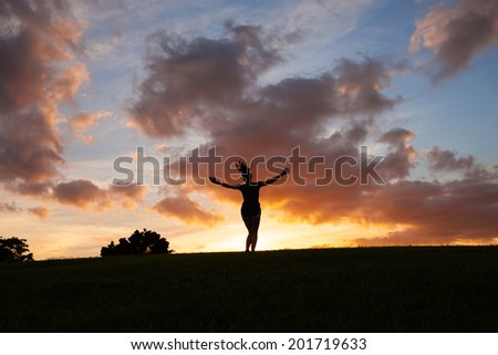 Free happy woman enjoying nature. Silhouette of woman dancing outdoors. Enjoyment. Freedom concept. - stock photo