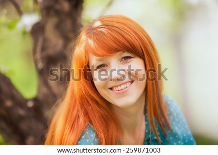 Free Happy Woman with Gorgeous Red Hair Enjoying Nature. Beauty Young Girl Outdoor in Spring Garden. Freedom concept. Healthy Smiling Girl over Green Flowers Nature Background. Apple-trees in Blossom - stock photo