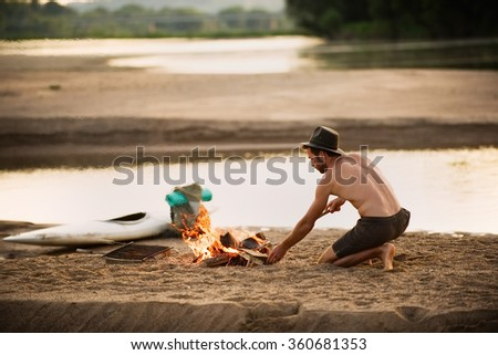 Free man making fire on the beach. A shirtless man with beard and hat is, on his knees, lightening a fire with wood. He is preparing for the night with his backpack and kayak close to him - stock photo