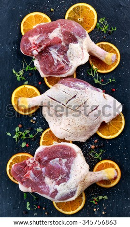 Free range Duck legs with oranges and herbs on old blue stone table. Preparing to cook. - stock photo