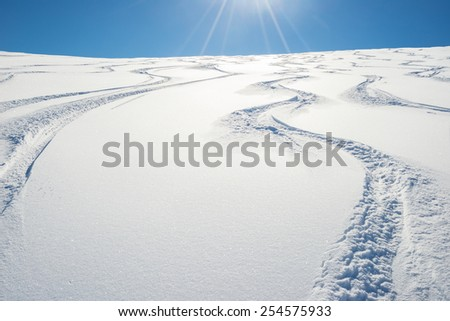 Free ride ski tracks on snowy slope. Shot taken in backlight from below. Fresh powder snow in a bright day of winter season. Concept of freedom. - stock photo