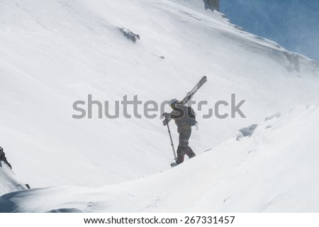 Free ride Skier Holding his Ski in a Windy Winter Mountain - stock photo