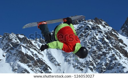 Free ride snowboarder performing a full loop and board grab. In the background snow covered high mountains and a blue sky - stock photo