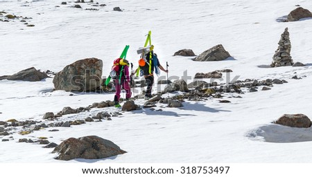 Free-riders ski climbers at the mountain summit in scenic Tian Shan range in Kyrgyzstan, Ala-Archa national park - stock photo