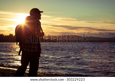 free silhouette man standing near the lake among the mountains, clouds, backlit at sunset  - stock photo