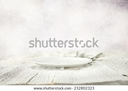 free space of plate and white snow on wooden table top  - stock photo