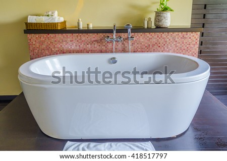 free standing contemporary ceramic bath tub and stone tile wall - stock photo