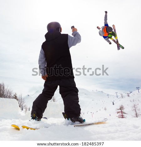 Free style skier performing a high jump. Buddy filming it on a Gopro camera. Ski lifts in the mountains in the background. - stock photo