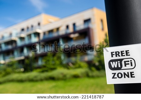 Free wi-fi zone sign in the public park in front of modern block of flats - stock photo