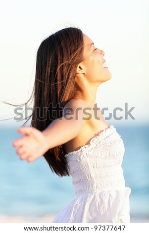 Free woman - freedom concept of happy woman in spring time standing carefree in summer dress on beautiful beach. Pretty mixed race caucasian / chinese asian girl outdoors. - stock photo