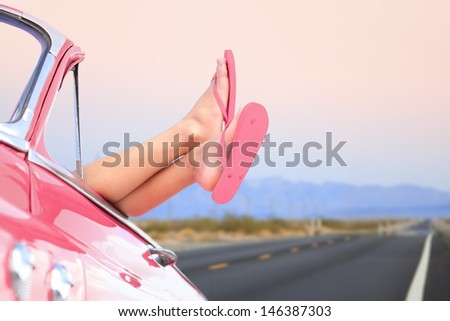 Freedom car travel concept - woman relaxing with feet out of window in cool convertible vintage car. Girl relaxing enjoying free holidays road trip. - stock photo
