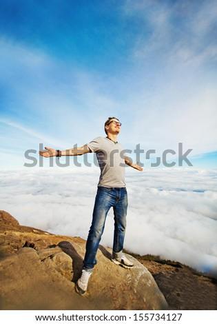 freedom concept: man on the peak of mountain - stock photo