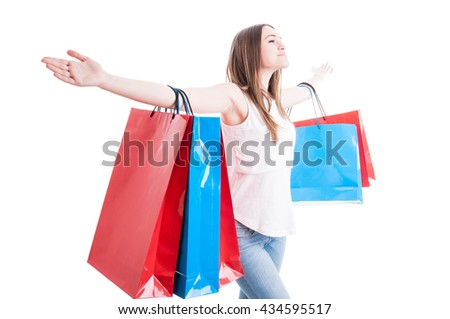 Freedom concept with beautiful shopaholic standing with arms wide open enjoying her leisure isolated on white background - stock photo