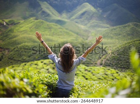 freedom girl with hands up in mountains    - stock photo