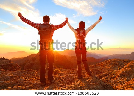 Freedom - Happy couple cheering and celebrating. Hiking man and woman raising arms excited in celebration outdoors. Hikers at sunset in mountain enjoying mountain top summit and success. - stock photo