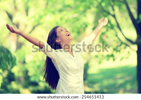 Freedom happy woman feeling alive and free in nature breathing clean and fresh air. Carefree young adult dancing in forest or park showing happiness with arms raised up. Spring allergies concept. - stock photo