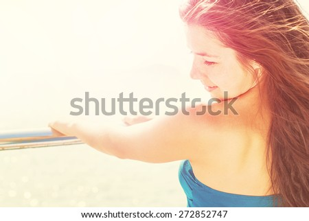 Freedom Happy Young Girl on a Pier. Outdoors. Long Hair Blowing in the Wind. Warm Color Tones - stock photo