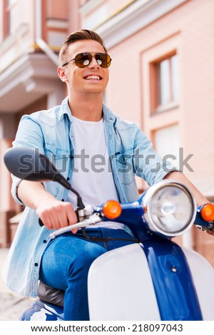 Freedom is in his veins. Low angle view of handsome young man in sunglasses riding scooter along the street and smiling  - stock photo