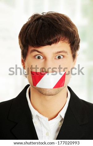 Freedom of speech concept. Young handsome businessman with red and white tape on his mouth. - stock photo