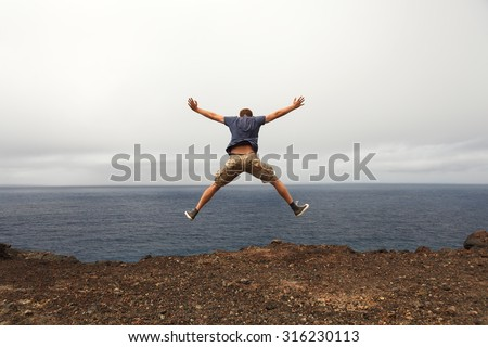 Freedom or adventure concept - jump of young man from a seaside cliff - stock photo