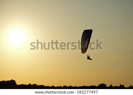 freedom paraglider at sunset - stock photo