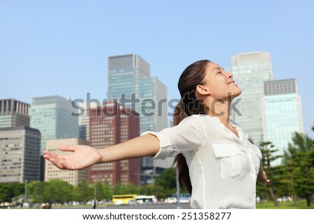 Freedom success businesswoman carefree in urban Tokyo, japanese city skyline - Success concept. Happy carefree business Asian woman arms open up in the sky, Japan. - stock photo