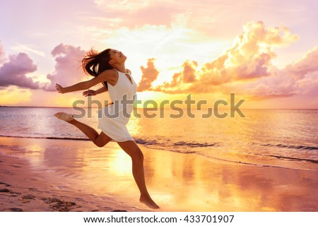 Freedom wellness well-being happiness concept. Happy carefree Asian woman feeling blissful jumping of joy on peaceful beach at sunset. Serenity, relaxation, mindfulness, stress free concepts. - stock photo