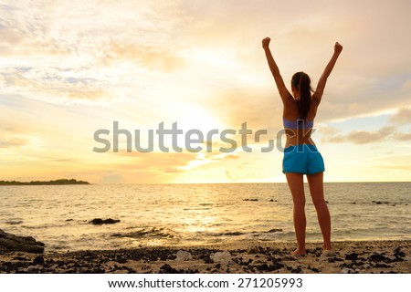 Freedom winning woman cheering at sunset beach. Success concept with female adult from the back arms up at the sky looking at the ocean feeling free and successful. Achievement of her life. - stock photo