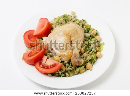 Freekeh salad with chickpeas, onion, parsley, celery, and a lemon juice and olive oil dressing, and a chicken leg with tomato - stock photo