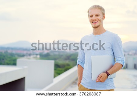 Freelance and technology. Outdoors portrait of handsome young man holding laptop computer. - stock photo