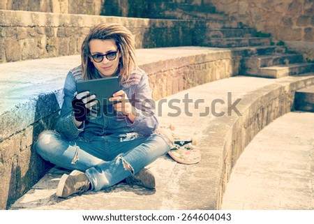 freelancer guy with dreadlocks sitting on staircase with digital tablet typing message warm filter applied - stock photo
