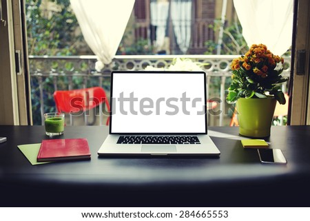Freelancer needs workstation, workplace with laptop, smart phone, notebook and pot of flowers, open computer with blank copy space screen for information or content, on-line learning or distance work - stock photo