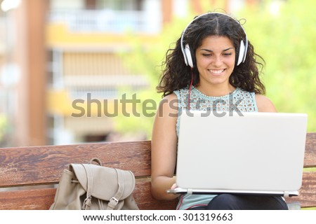Freelancer working with a laptop and headphones sitting on a bench in a park - stock photo
