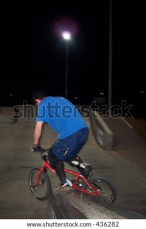 freestyle BMX rider does a pedal grind down ledge at skate park - stock photo