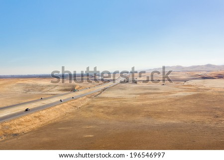 Freeway cuts though pastures that are brown in color and dry out due to a drought in central California.   - stock photo