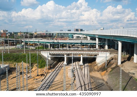 freeway overpasses and train tracks, on the background of industrial city, blue cloudy sky - stock photo