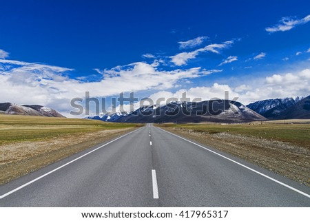 freeway receding to the horizon under a blue sky among the high snow-capped mountains - stock photo