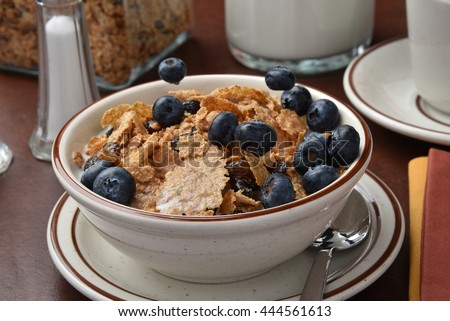 Freeze mortion shot of blueberries being dropped onto a bowl of cereal - stock photo