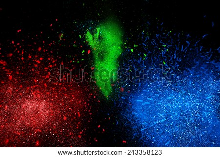 Freeze motion of colorful powder exploding, isolated on black, dark background. Abstract design of dust cloud. Particles explosion, screen saver wallpaper with copy space. Vivid yellow green red ash  - stock photo
