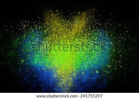 Freeze motion of colorful powder exploding, isolated on black, dark background. Abstract design of dust cloud. Particles explosion screen saver wallpaper with copy space. Vivid yellow blue green ash - stock photo