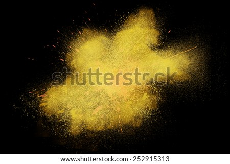 Freeze motion of colorful yellow powder exploding isolated on black dark background. Abstract design of color dust cloud. Particles explosion screen saver, wallpaper, brush - stock photo