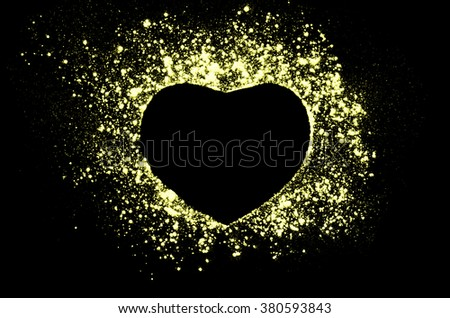 Freeze motion of heart shaped yellow powder on black, dark background. Abstract design of dust cloud. Particles explosion screen saver, wallpaper with copy space. Love, passion, feelings concept. - stock photo