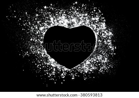 Freeze motion of white powder on black dark background. Abstract design of dust cloud. Particles heart shaped explosion screensaver, wallpaper with copy space. Love, passion, care concept - stock photo