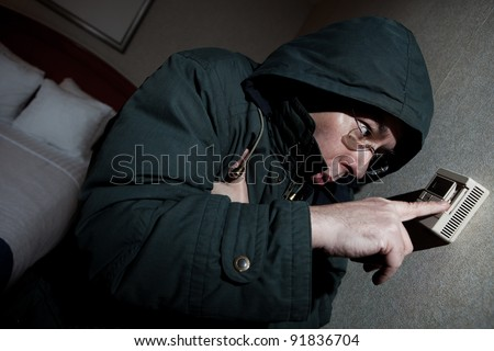 Freezing man adjusting thermostat - stock photo