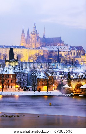 Freezy foggy night snowy Prague with gothic Castle and Charles Bridge - stock photo
