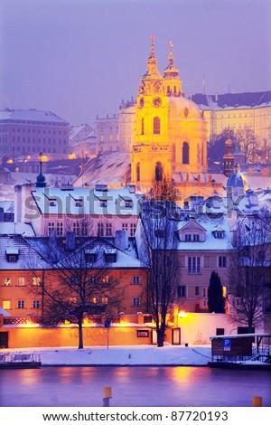 Freezy foggy night snowy Prague with St. Nicholas' Cathedral, Czech Republic - stock photo