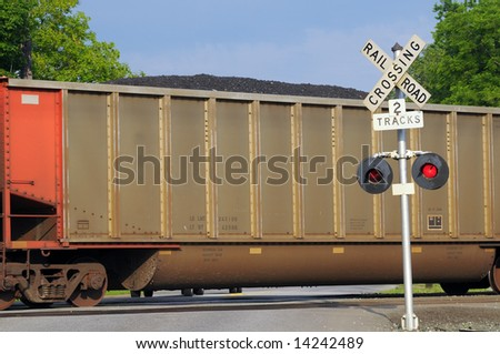 Freight car filled with coal passes over a grade crossing with warning signal - stock photo